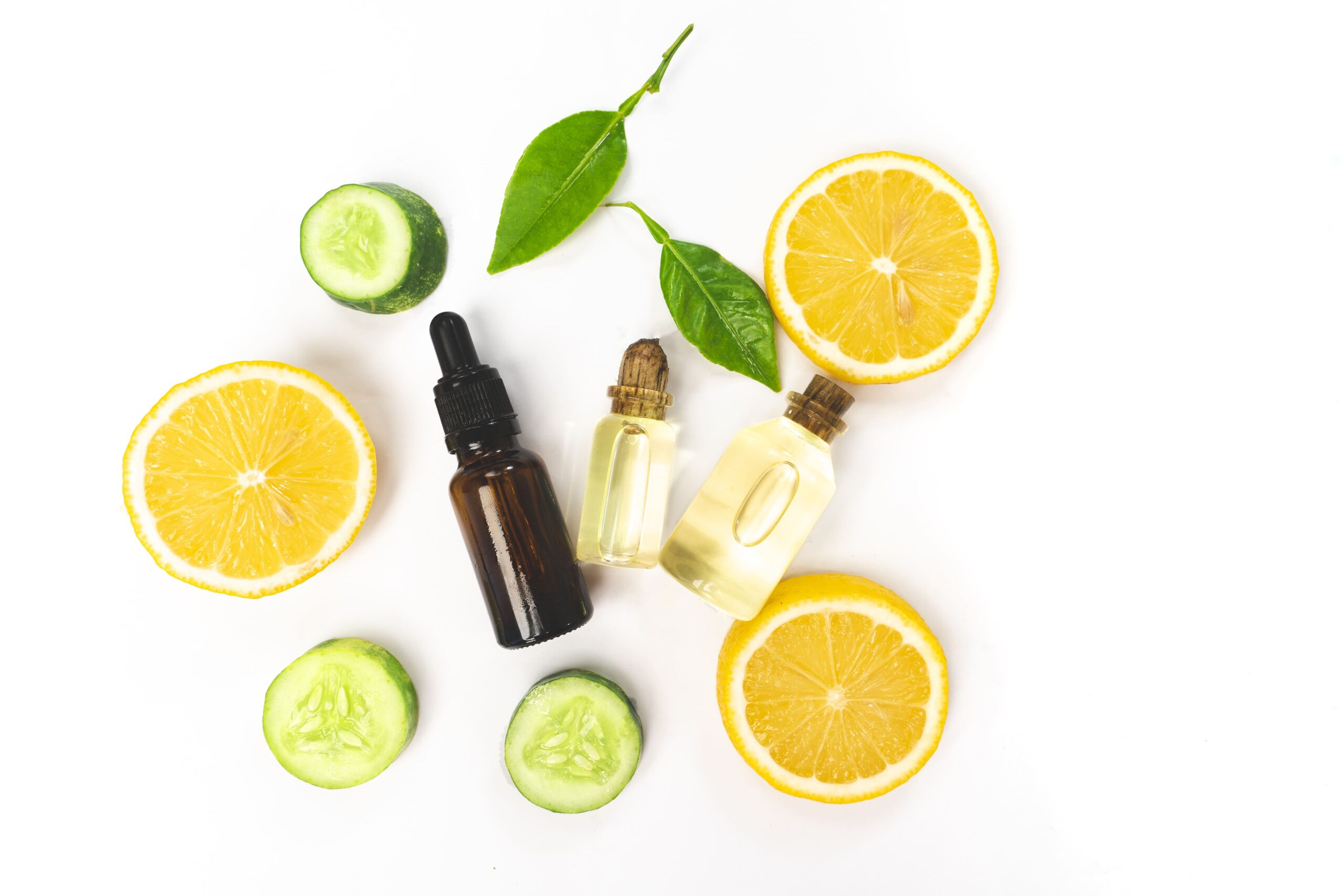 essential fruit oil on bottle with lemon fruits with leaf on white background 1 1 scaled